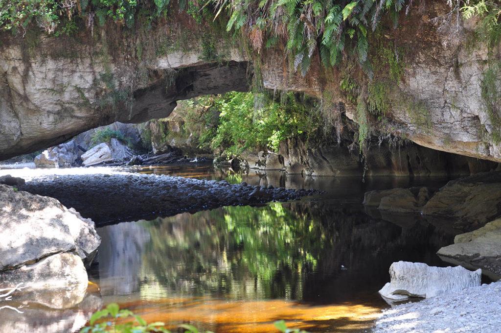 nieuw-zeeland-honeycomb-moria-arch-spiegeling-rivier
